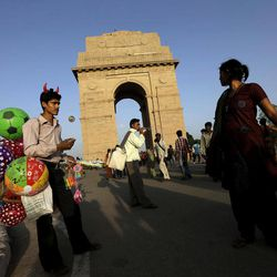 In this Monday, Sept. 24, 2012 photo, Indian vendors look for customers at the India Gate in New Delhi, India. The towering India Gate, New Delhi's answer to the Arc de Triomphe, stands in a massive park at the heart of the city. The sandstone and granite memorial commemorates the soldiers in the British Indian Army killed in World War I and in fighting in Afghanistan.