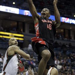 Toronto Raptors' Ben Uzoh (18) shoots past Milwaukee Bucks' Drew Gooden during the first half of an NBA basketball game Monday, April 23, 2012, in Milwaukee.