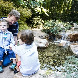Dash Johnson, 4, a patient at Primary Children's Hospital, sits on his father's lap while throwing money into a pond during the reopening of the Angel Garden at the hospital in Salt Lake City on Monday, Aug. 1, 2016. The redesigned garden includes more than 1,000 new plants and trees, as well as legacy monuments, including the Butterfly Angel statue, a commissioned 5-foot bronze. Dash's family spearheaded renewal project.