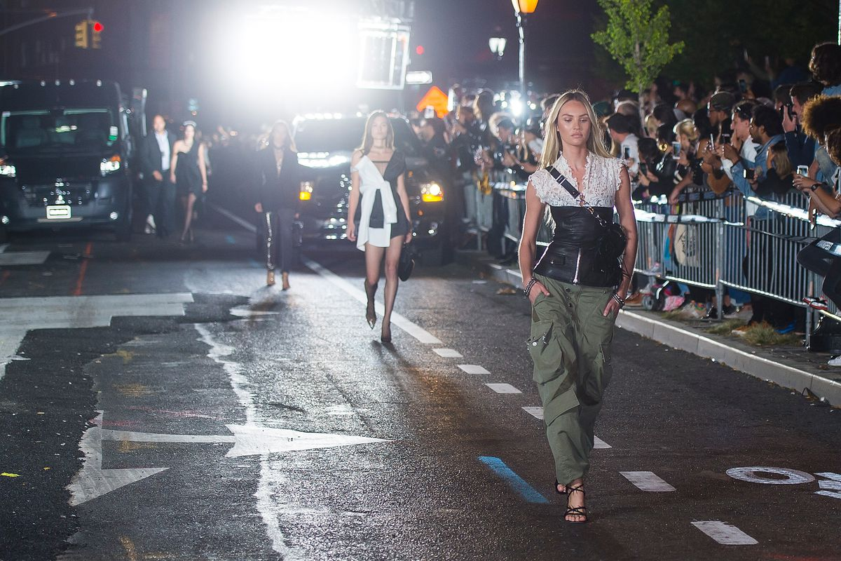 A model walks down the street wearing cargo pants and a white lace and black leather top.