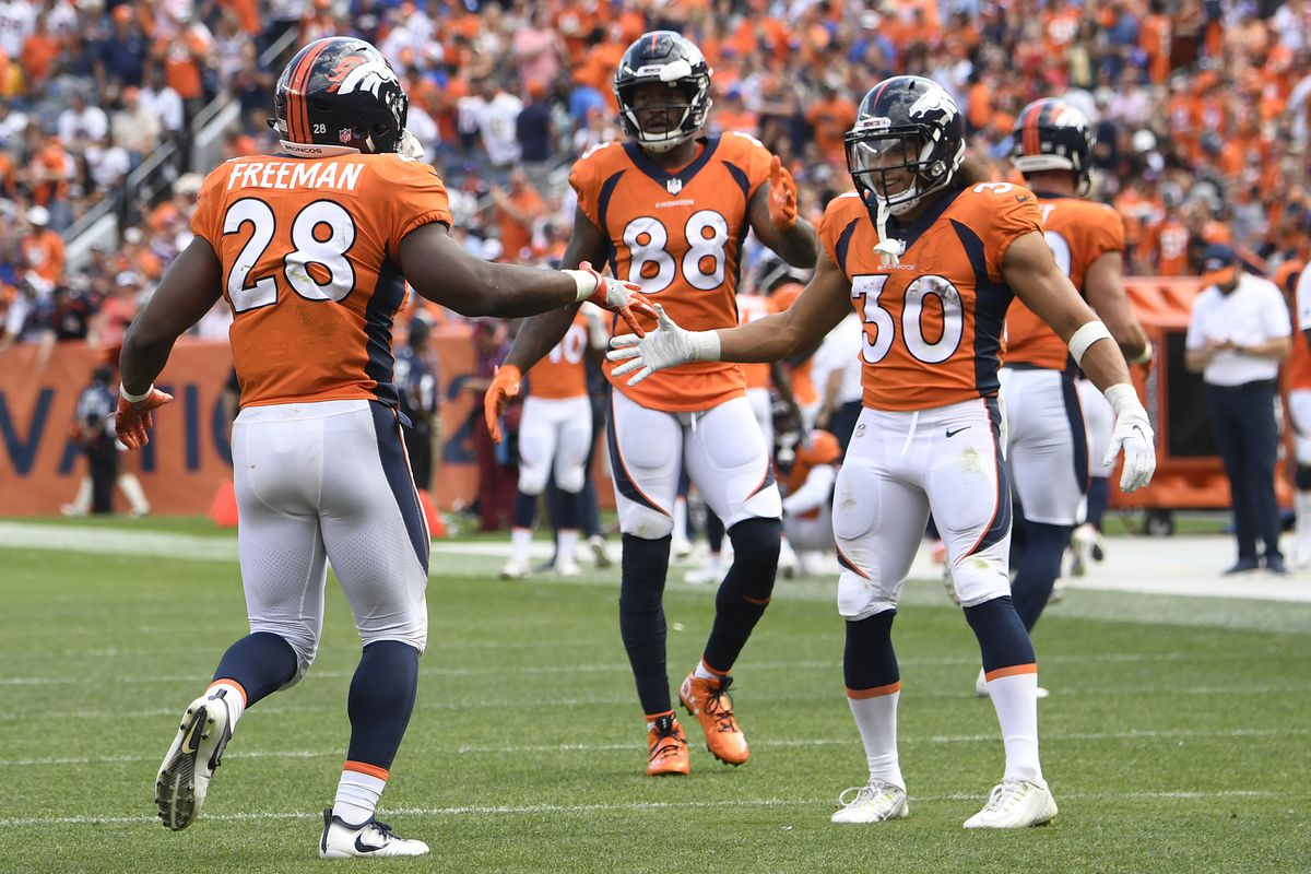 Royce Freeman of the Denver Broncos celebrates scoring a touchdown with Phillip Lindsay during the third quarter against the Oakland Raiders.