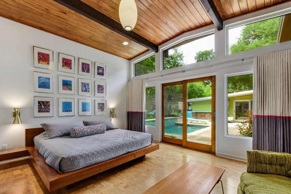 A master bedroom with platform bed, gray linens, wood floors, and doors that head to the backyard pool.