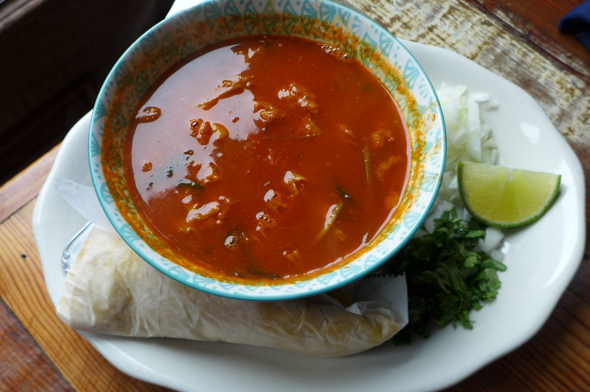 Red tripe soup with lime wedge, herbs and onions, and tortillas on the side.