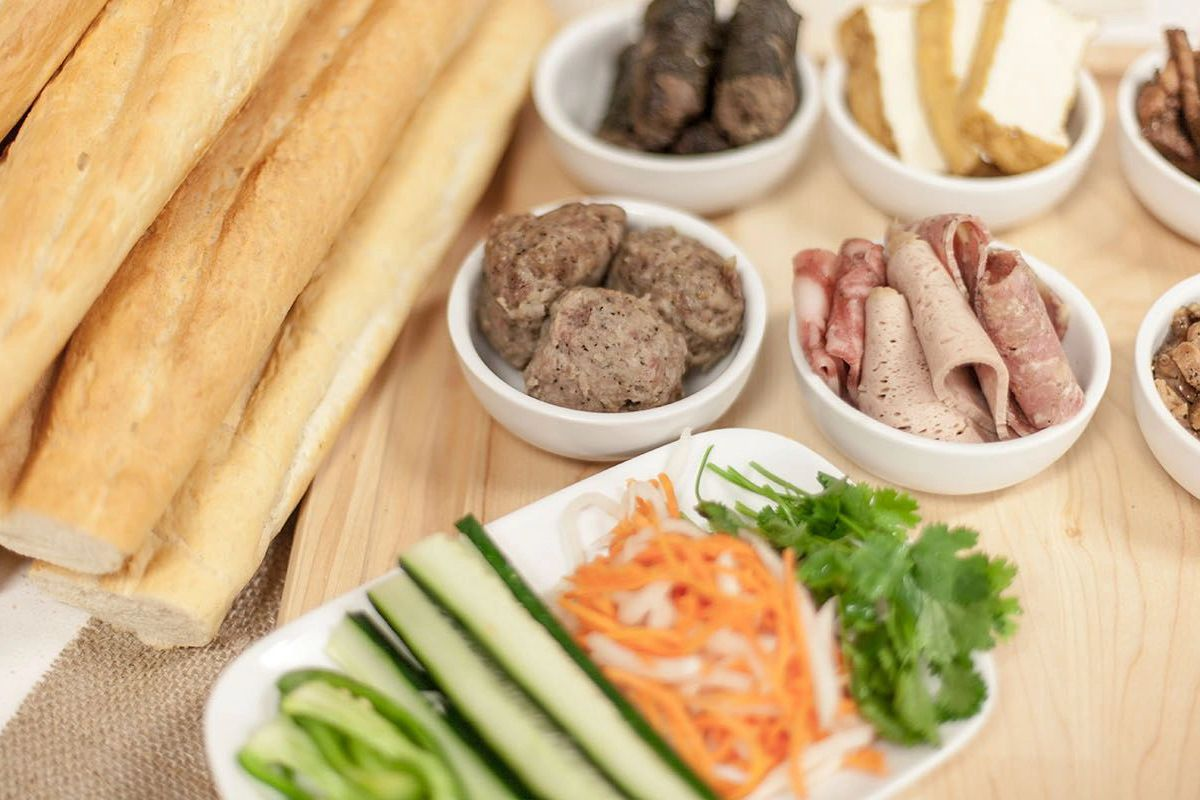 A spread of sliced vegetables, jambon, head cheese, pork belly, and other fixins