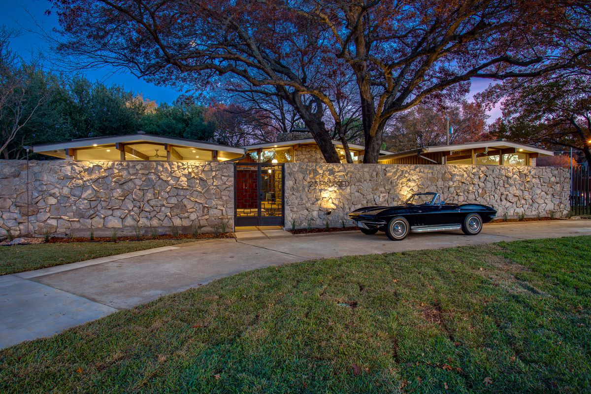 Night time shot of low-slung home with three broadly sloping gabled roofs and a stone wall protecting it. An old-fashioned car sits in the driveway.