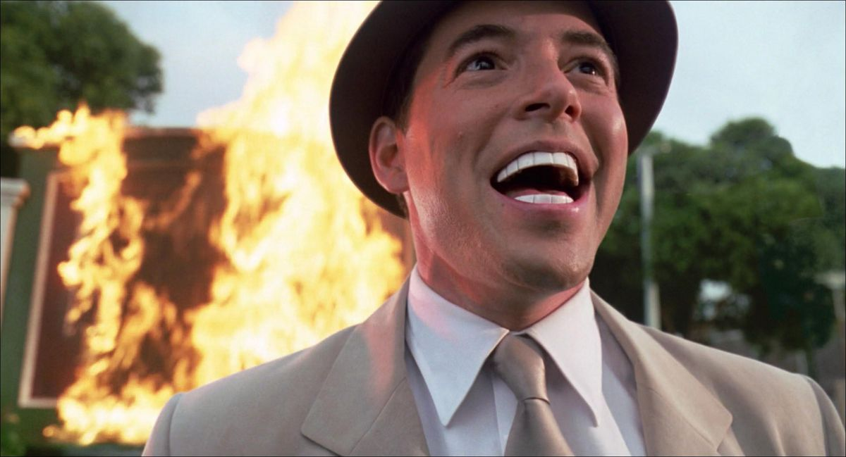 matthew broderick laughs like a madman with perfect white teeth while standing in front of a fire in Inspector Gadget