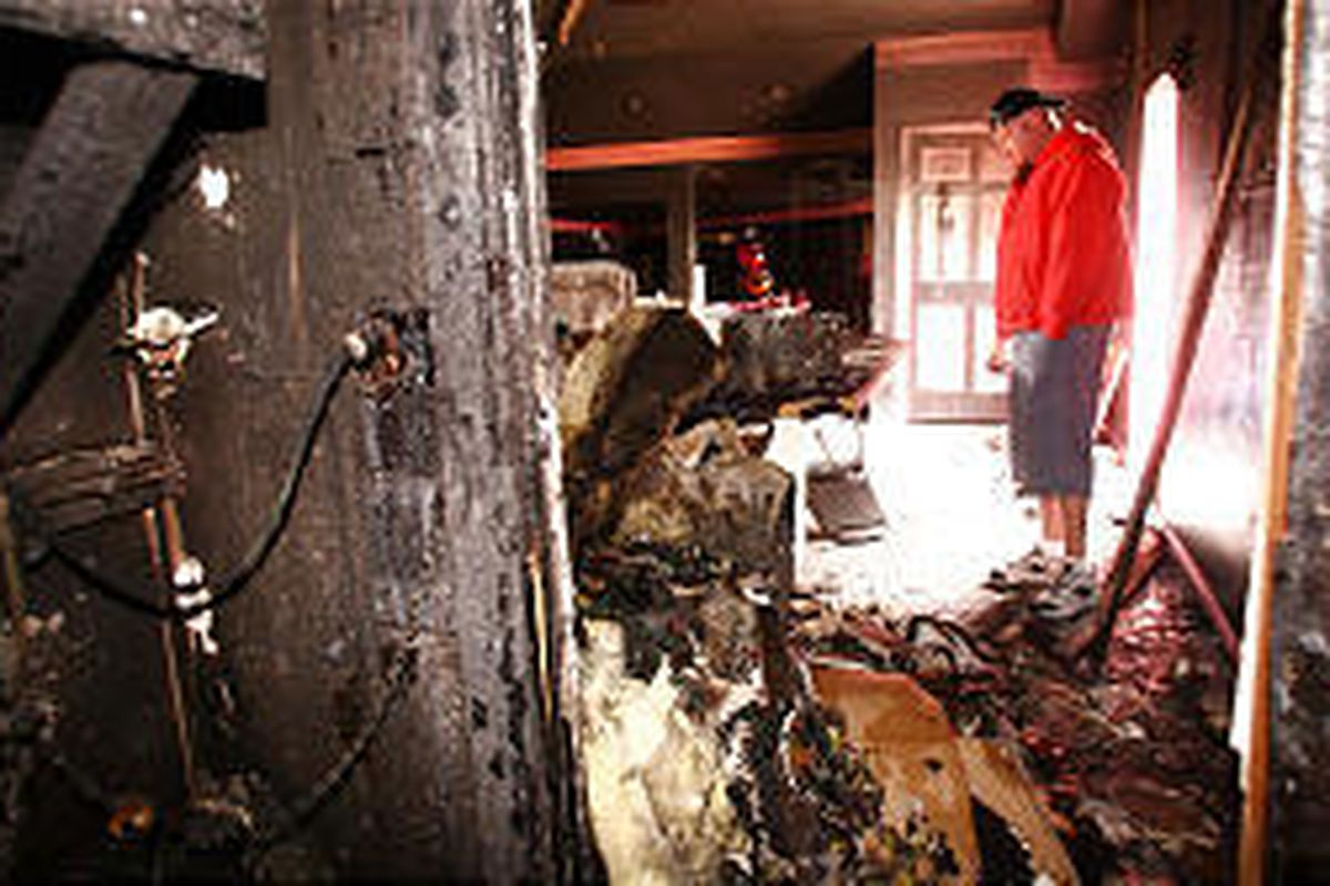 Casey Kalm, who owns Pinky's, looks over fire damage. He estimated that $5,000 in cash had been stolen.