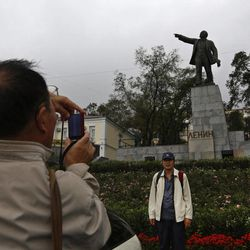 A Chinese tourist poses for a photo in front of a statue of Lenin in the eastern Russian city of Vladivostok Wednesday, Sept. 5, 2012. Once a mysterious closed city during Soviet times, Vladivostok is ready to strut in the world spotlight as host of the Asia-Pacific Economic Cooperation summit. Russia has splashed $20 billion preparing for the summit in Vladivostok, its largest but long-neglected Pacific port, as part of a grand plan to become a bigger player on Asian markets.