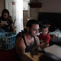 """In this Monday, Aug. 1, 2011 photo, former skinhead Bryon Widner plays a video game as his son, Tyrson, watches and his stepdaughter, Mercedez, background left, folds laundry at their home. For 16 years, Widner was a glowering, swaggering, menacing vessel of savagery - an """"enforcer"""" for some of America""""™s most notorious and violent racist skinhead groups."""