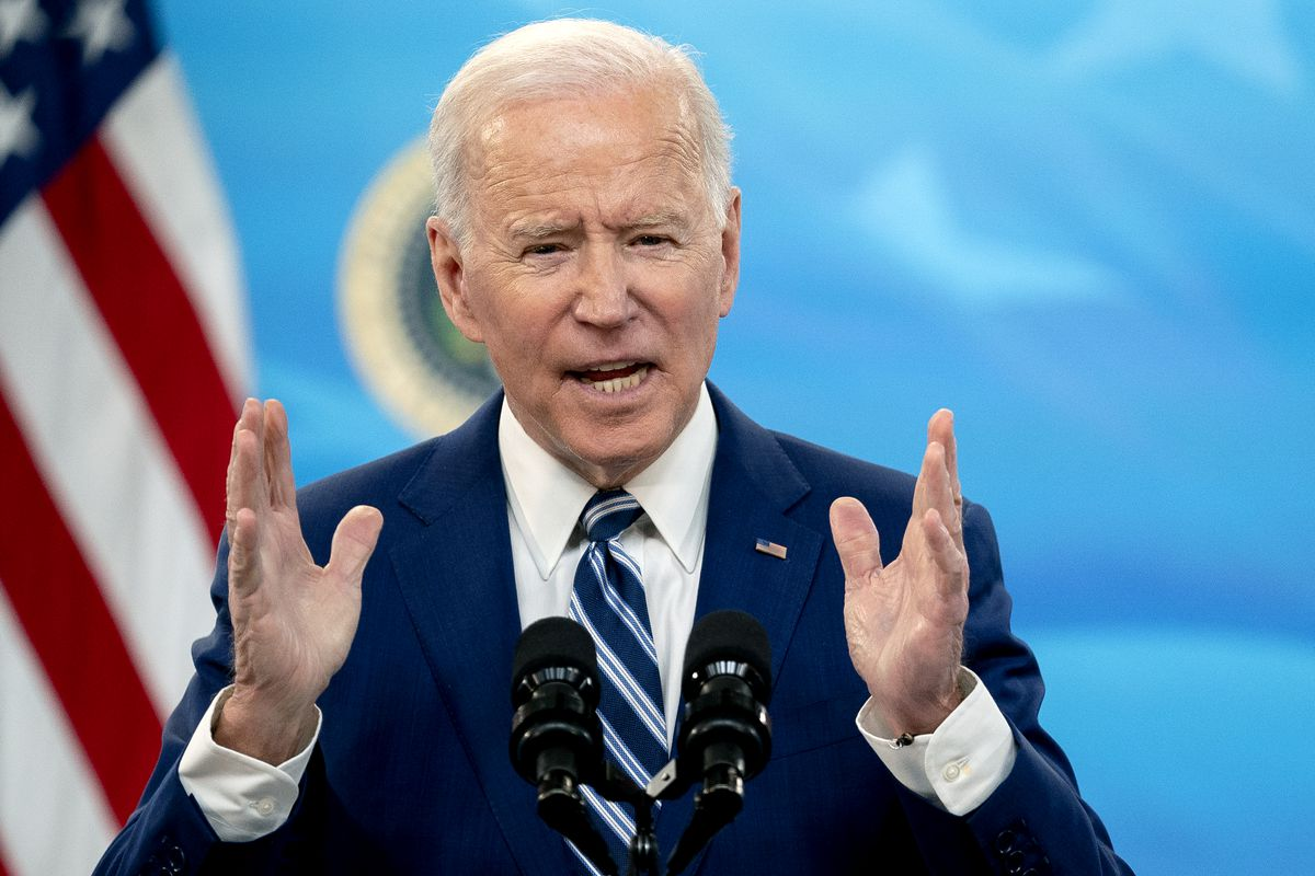 """President Biden onstage speaking into microphones and holding his hands in a """"this wide"""" gesture."""