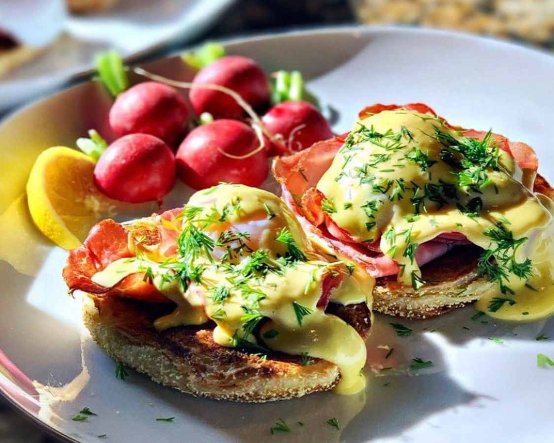 A version of eggs Benedict covered with fresh herbs, featuring Model Bakery's English muffins