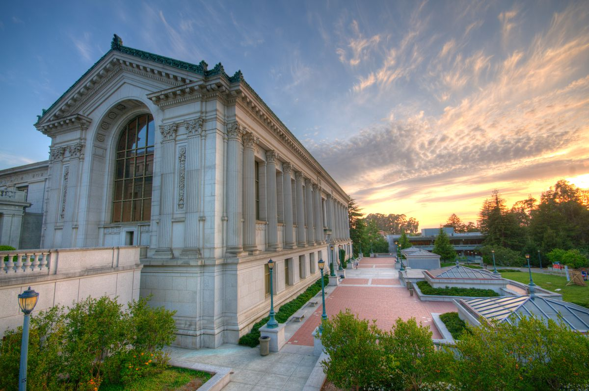 The exterior of the Doe Library in California. The facade is white stone with columns. There is a sunset in the sky.