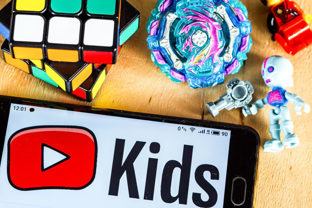 A phone screen showing the YouTube Kids logo. Also in the picture are a Rubik's cube and other colorful small toys.
