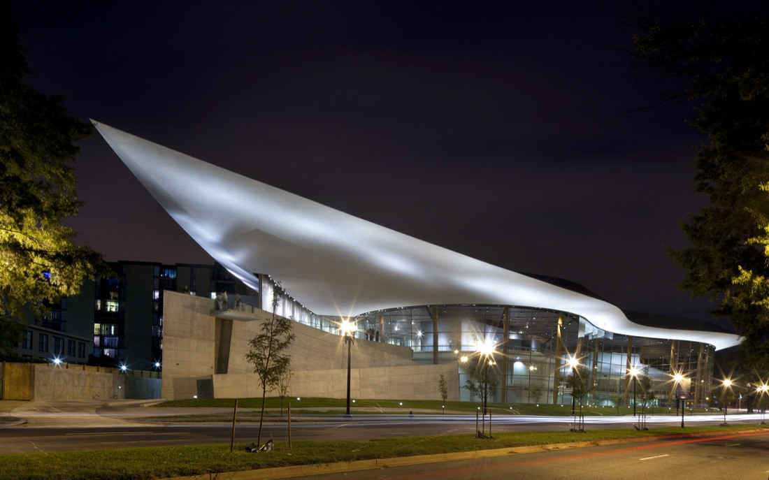 The exterior of Washington D.C.'s Arena stage. The roof is white and slopes upward. The walls are glass.