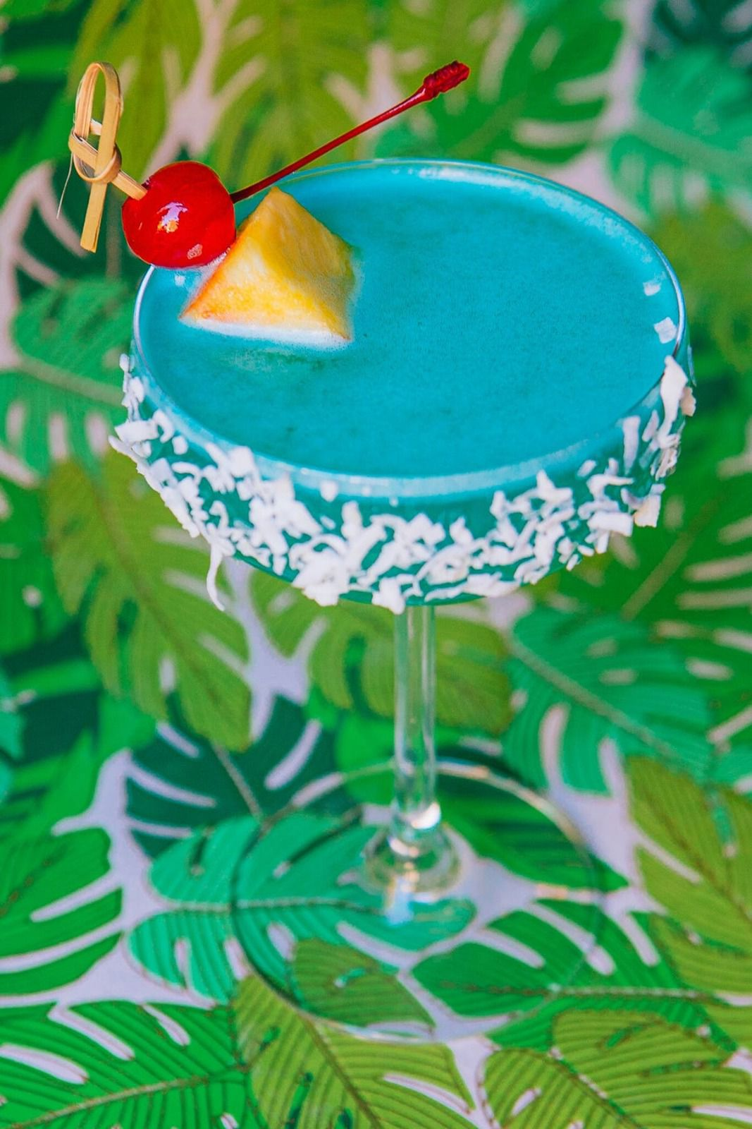 A blue drink with a cherry and piece of pineapple skewered in. Coconut flakes are pasted along the rim of the glass.