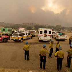 Members of the US Forest Service's Blue Ridge Hotshots, foreground, and other firefighters watch as the Yarnell Hill Fire advances on the town of Yarnell, Ariz., Sunday, June 30, 2013. The crew vehicles (buggies) for the Granite Mountain Hotshots are the white vehicles parked at center and right. 18 members of the Granite Mountain crew were killed fighting the Yarnell Hill Fire. (AP Photo/The Arizona Republic, Tom Story)