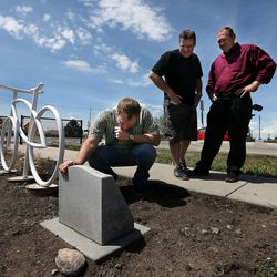 Brothers Mel, left, Allen and Jeremy Crow look at a memorial in honor of their father, Douglas Crow, in Provo, Wednesday, May 20, 2015. Douglas Crow was an avid cyclist who died Feb. 13, 2013.