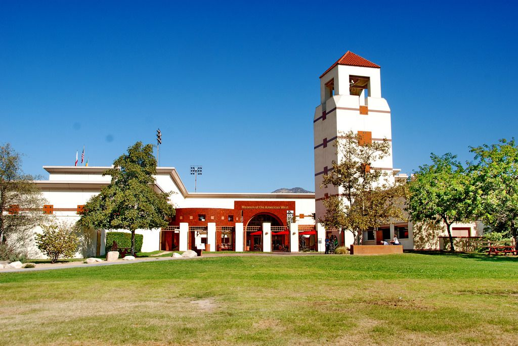 The exterior of the Autry Museum of the American West. The facade is red and white with a tower and columns on the front.