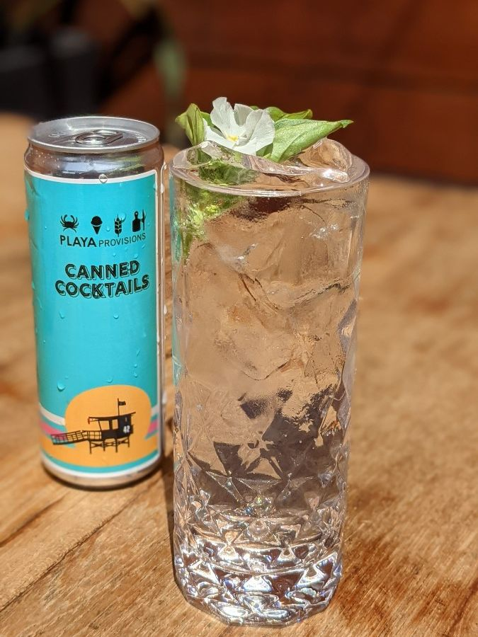 Surfin' Seltzer at Playa Provisions, a blue canned cocktail to the side and a highball glass filled with the clear seltzer drink and topped with leaves and a flower.