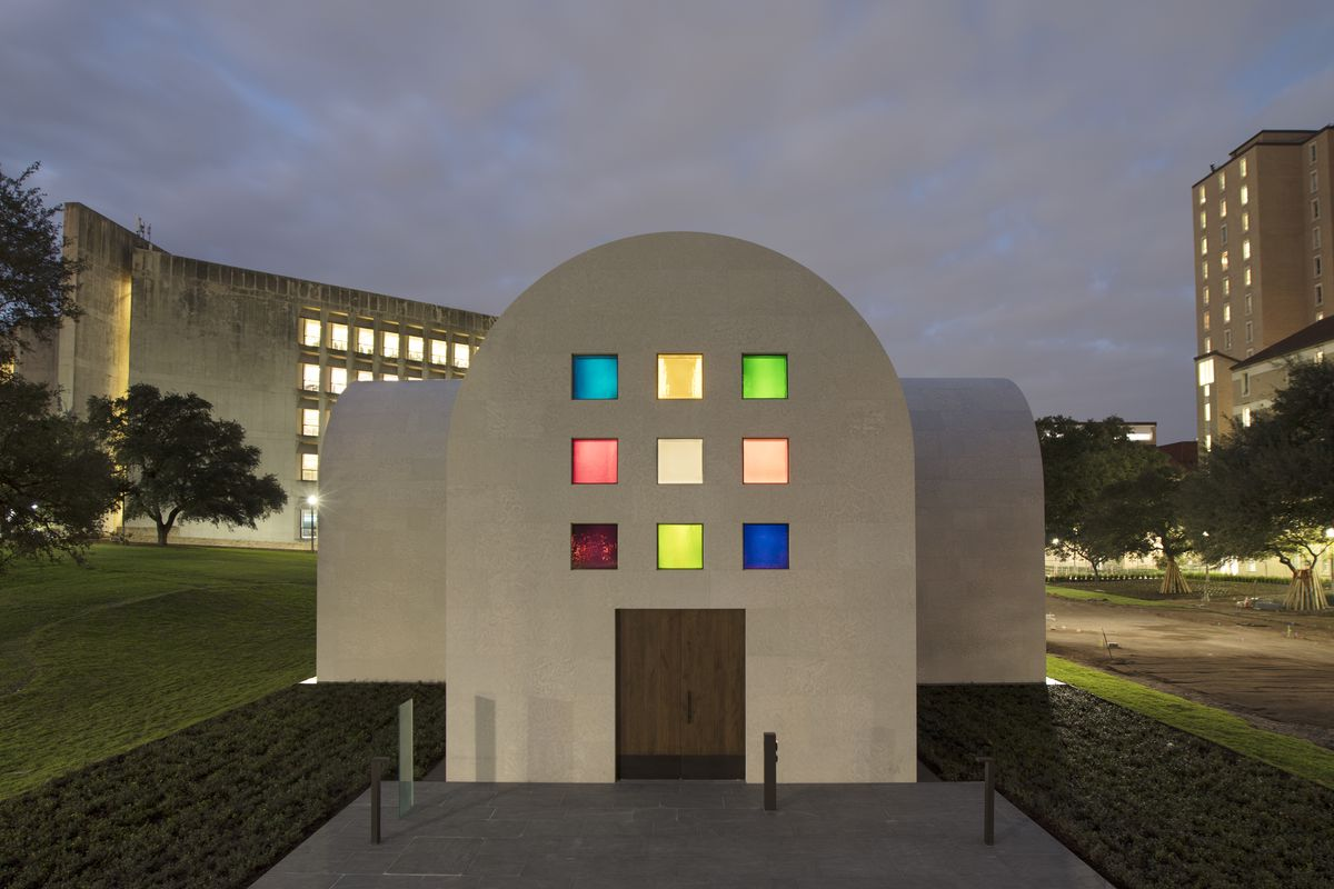 Chapel-like stone artist-designed building with colored glass windows, black and white marble panels, and redwood totem
