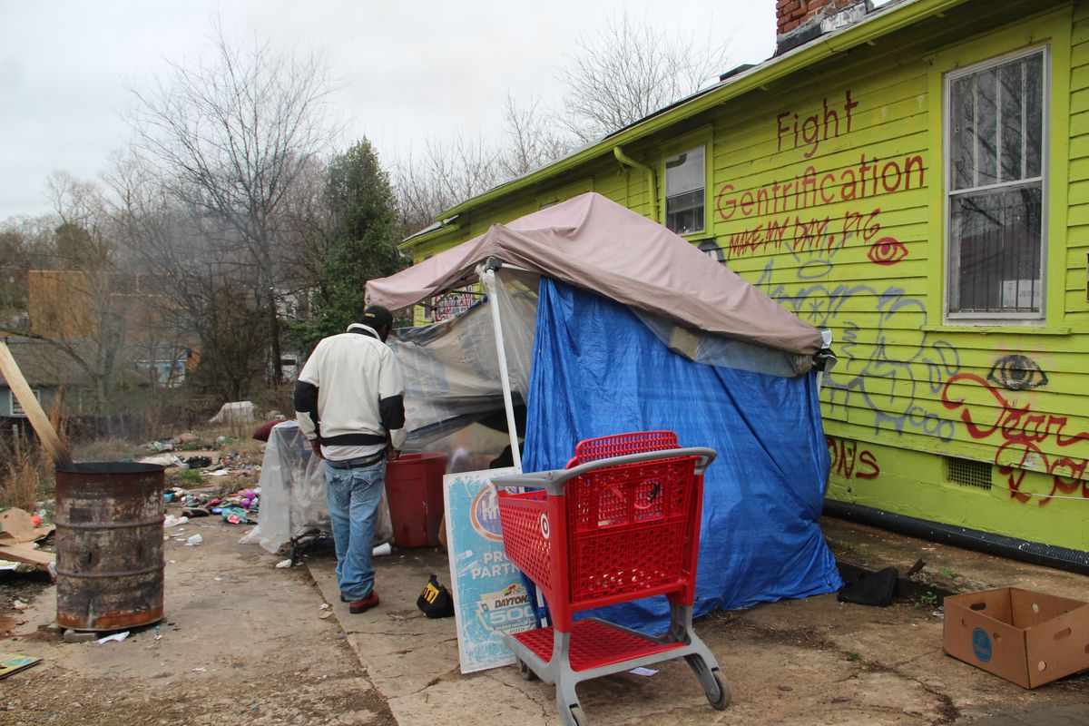 A tent with a shopping cart beside a yellow-painted home.