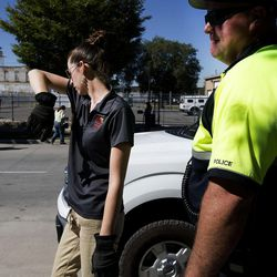 Karla Bartholomew, health scientist with the Salt Lake County Health Department, wipes the perspiration from her face while cleaning up the encampments on 500 West with Salt Lake City police officer Cody Orgill on Wednesday, Sept. 28, 2016.