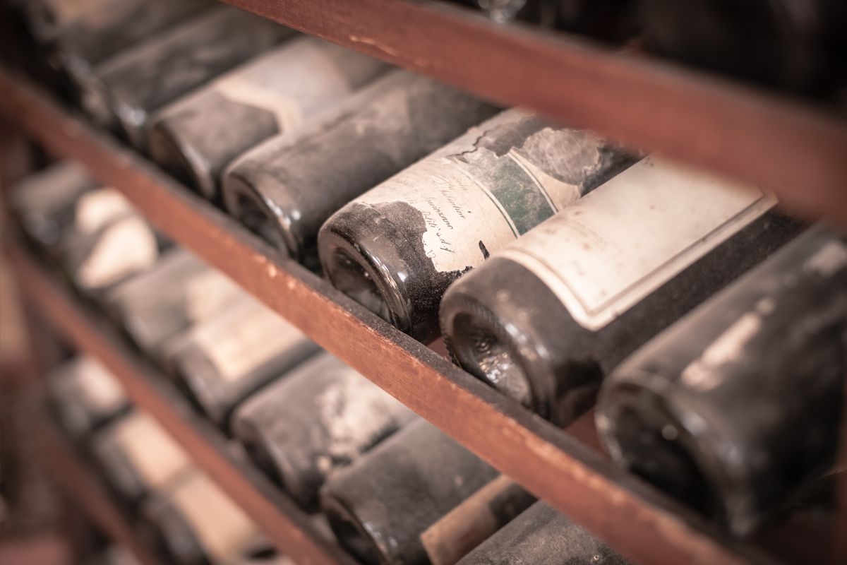 Several dust-caked old wine bottles laying sideways on wooden shelves