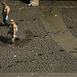 Armed military personnel slog through mud as they go door to door in hurricane-damaged neighborhood in Chalmette, La., Friday.