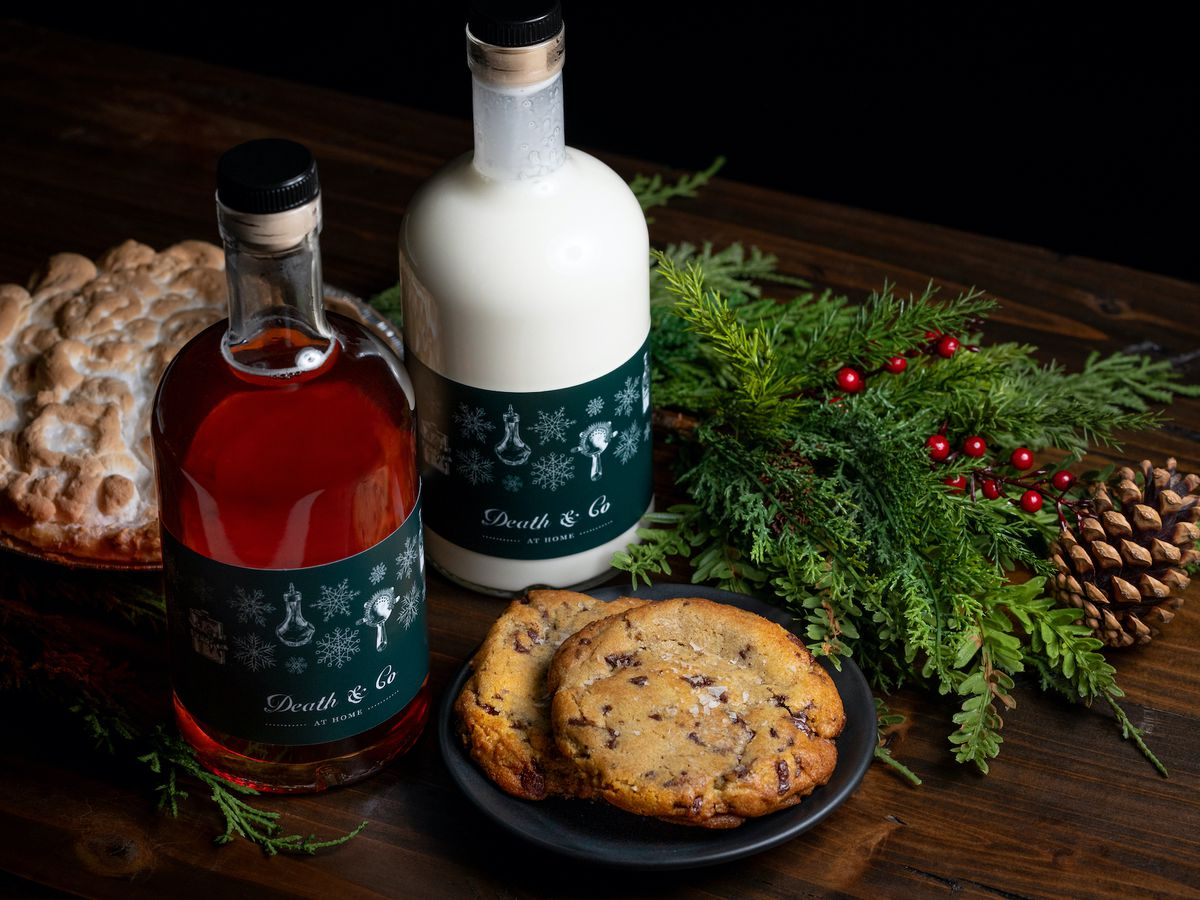 A table of cocktails in bottles with a holiday theme and cookies.
