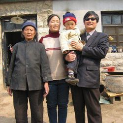 This undated photo provided by the China Aid Association shows blind Chinese legal activist Chen Guangchen, right, holding his son, Chen Kerui, with his wife Yuan Weijing, second from left, and his mother, left, in Shandong province, China. Chen, a well-known dissident who angered authorities in rural China by exposing forced abortions, made a surprise escape from house arrest on April 22, 2012, into what activists say is the protection of U.S. diplomats in Beijing, posing a delicate diplomatic crisis for both governments.