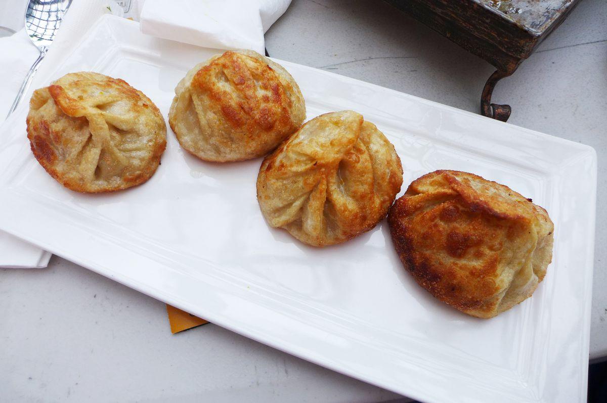 Four round fried dumplings shaped like purses on a white plate.