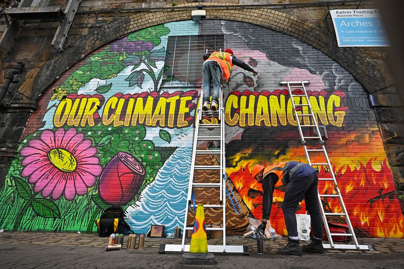 """Two painters, one on a ladder, create a mural on the side of a brick building titled """"Our Climate Is Changing."""" Half of the mural depicts flowers and blue sky, the other half shows fire and black clouds."""