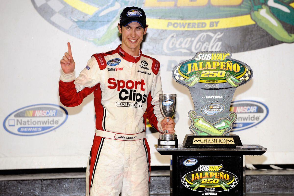 Joey Logano celebrates with the trophy after winning the NASCAR Nationwide Series Subway Jalapeno 250 at Daytona International Speedway on July 1.