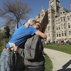 """Aaron Davidson, who is holding a """"Free Hugs"""" sign, gets a hug from Sharon Barlow as Utahns rally against a state stay-at-home request at the City-County Building in Salt Lake City on Saturday, April 18, 2020."""