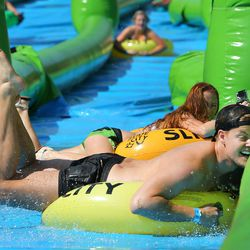 Aaron Nelson drags his face on the side matt as he and hundreds of others enjoy the sun and water Saturday, Aug. 22, 2015, as they participate in Slide the City, in Salt Lake City.