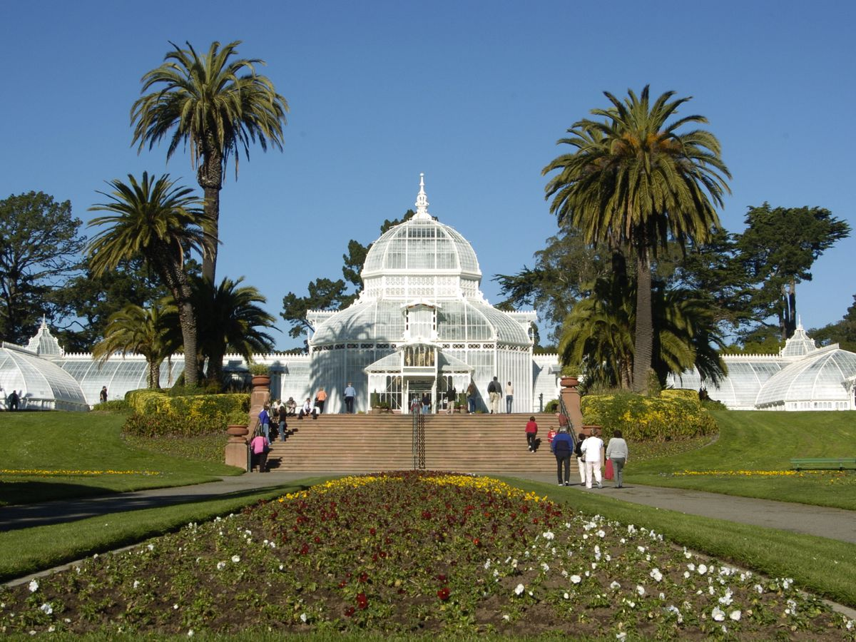 In the foreground is a flower garden. In the distance is a large white domed conservatory building. There are pam trees in front of the building.