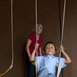 In this Friday, Sept. 7, 2012 photo, Judy Russell, left, watches her adopted grandson Daniel swing at at a restaurant in Guatemala City. Daniel was 18 months old when Russell's daughter, Jessica Hooker and her husband Ryan began the process to adopt him in Guatemala. They just got him at age 6. His is one of hundreds of adoption cases that were put in limbo five years ago, when the Guatemalan government declared a moratorium on international adoptions because of irregularities and fraud.
