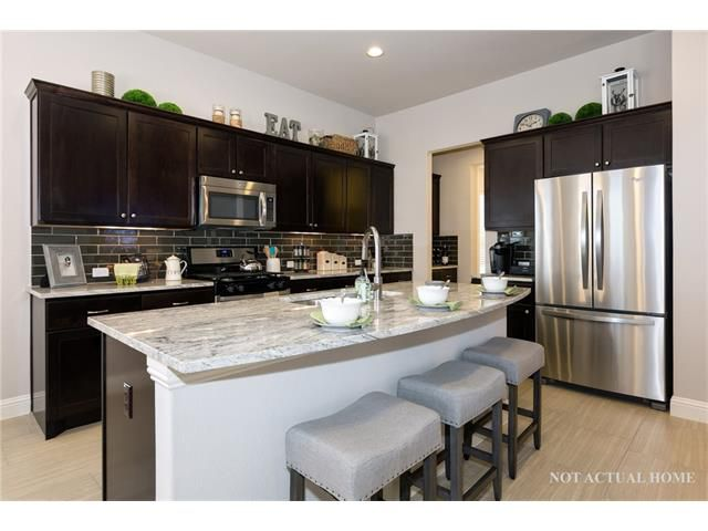 Small new condo kitchen with gray and brown color scheme, breakfast bar