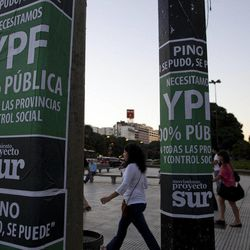 """People walk past signs reading in Spanish """"YPF, 100 percent public"""" in Buenos Aires, Argentina, Thursday April 19, 2012. Argentina's government showed no signs of backing down Thursday from expropriating a Spanish company's controlling stake in YPF, Argentina's formerly state-owned energy company, shrugging off international condemnation while finding overwhelming support for the plan in congress."""