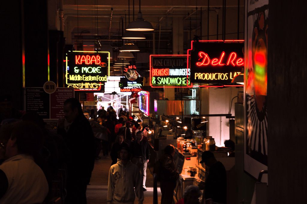 The interior of a food market. There are multiple neon signs with various names of restaurants on them.