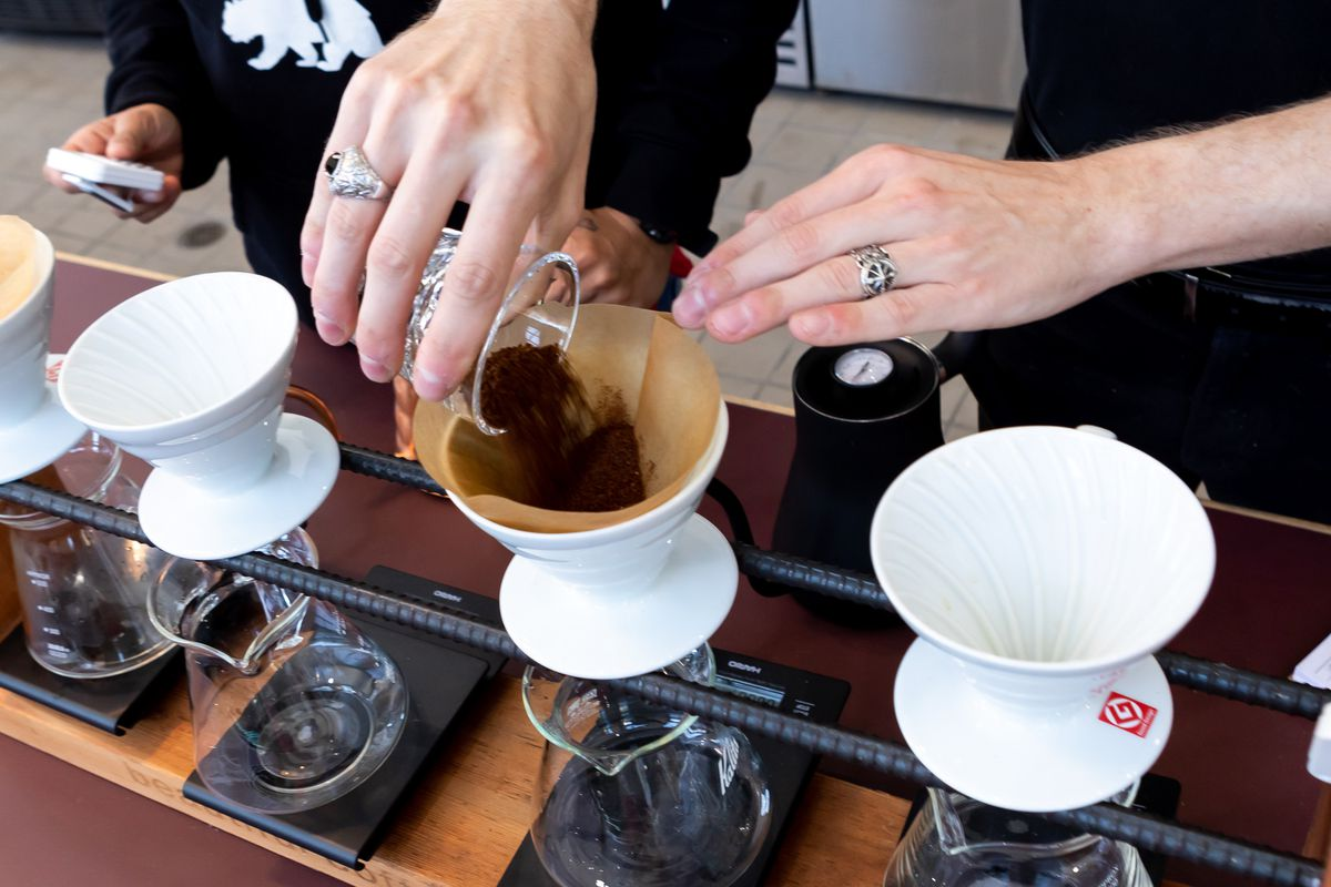 A Red Bay Coffee barista pours coffee into a funnel.