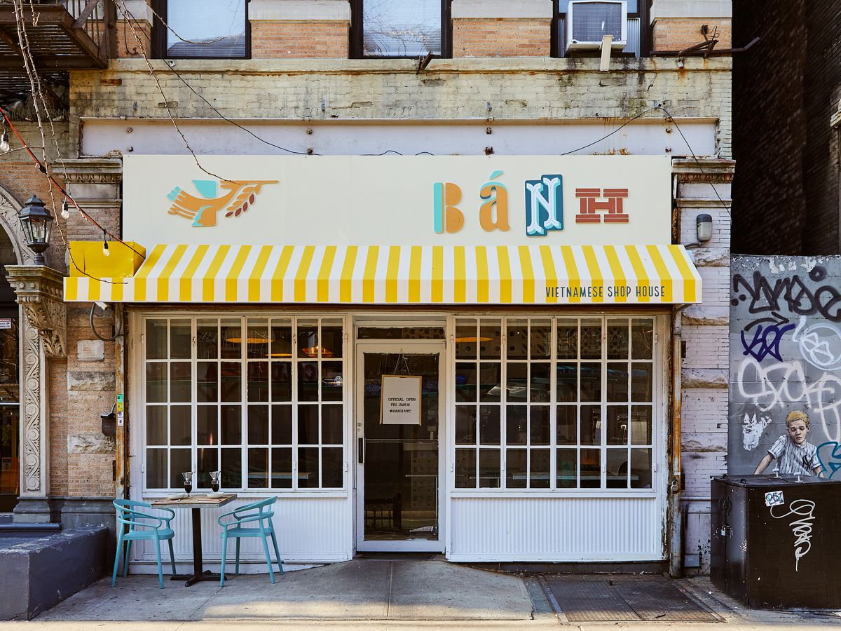 A colorful restaurant exterior with a yellow and white striped awning and white framed windows, with a teal blue set of chairs and a table set up outside