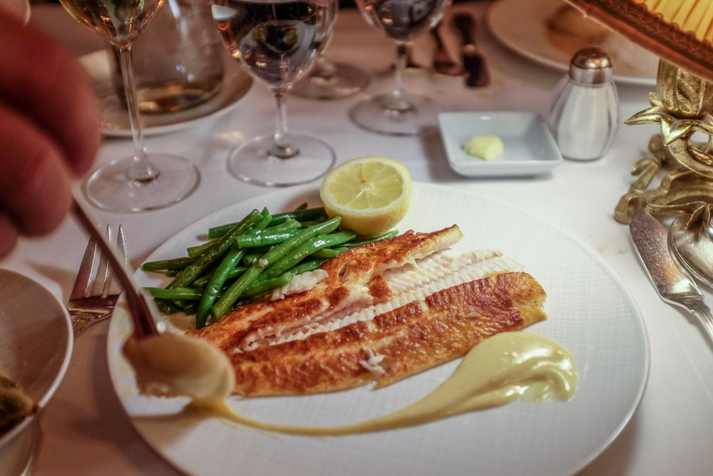 A white plate with a hand spooning sauce on it, next to fish, green beans, and a half lemon placed on the dish.