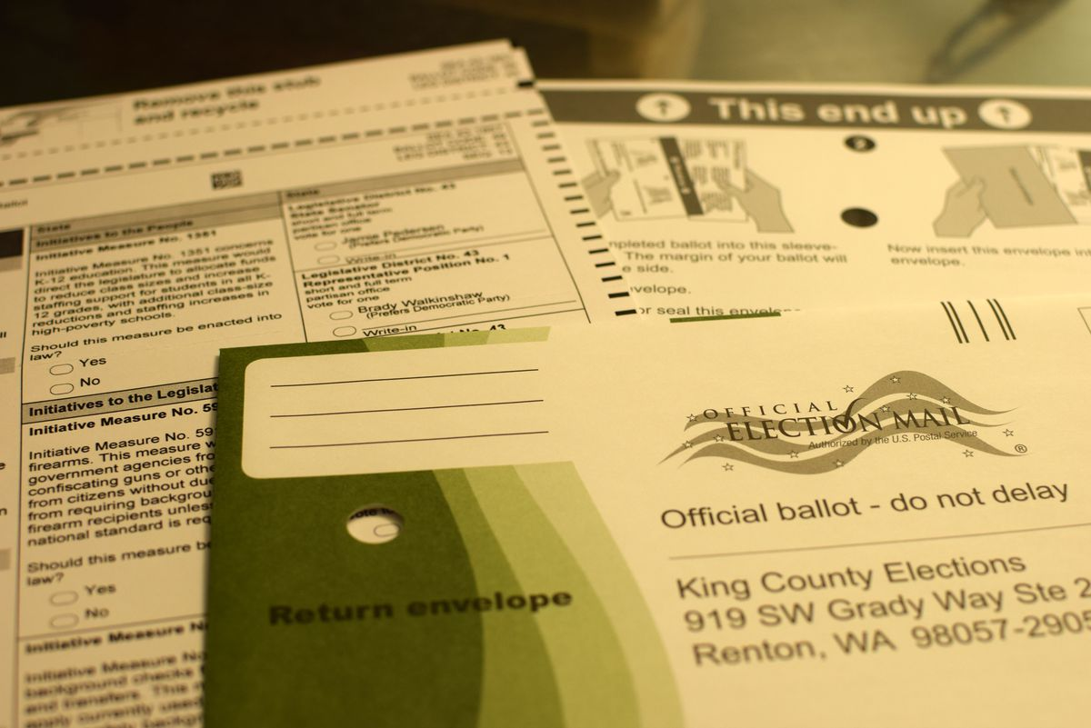 """Three pieces of paper: An envelope with a green design at the left side addressed to King County Elections. Behind that, a sheet of paper with multiple-choice questions. There's another that says """"This end up"""" behind that."""