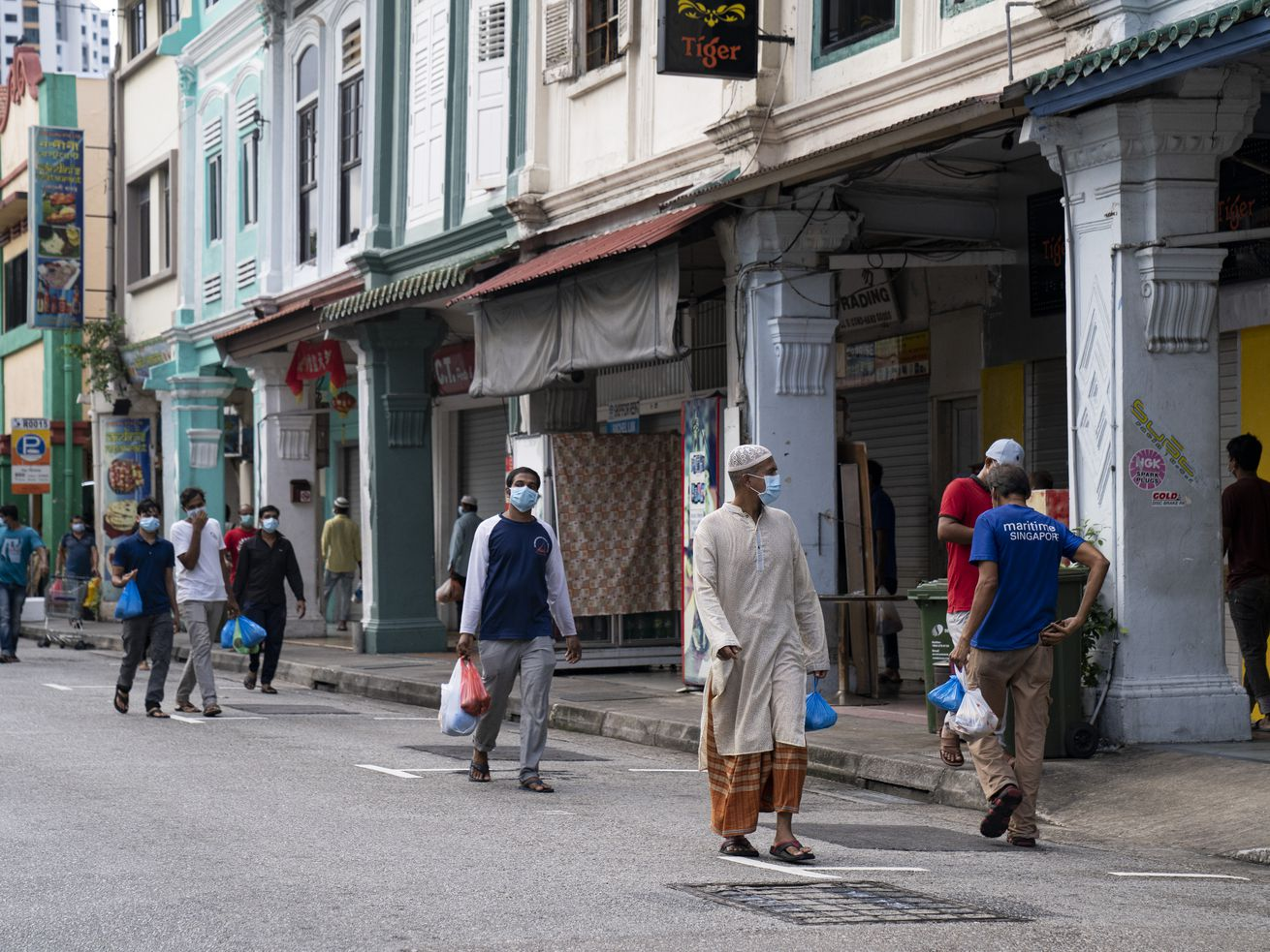 Migrant workers wearing protective masks return to their rented rooms in Little India after collecting free food distributed by NGOs on May 15, 2020, in Singapore.