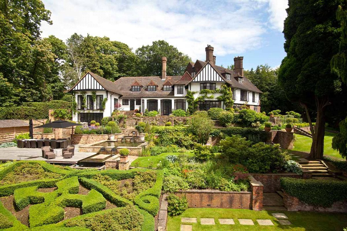 Exterior shot of Tudor-style house with multiple dormer windows and landscaped garden with fountain and hedges.