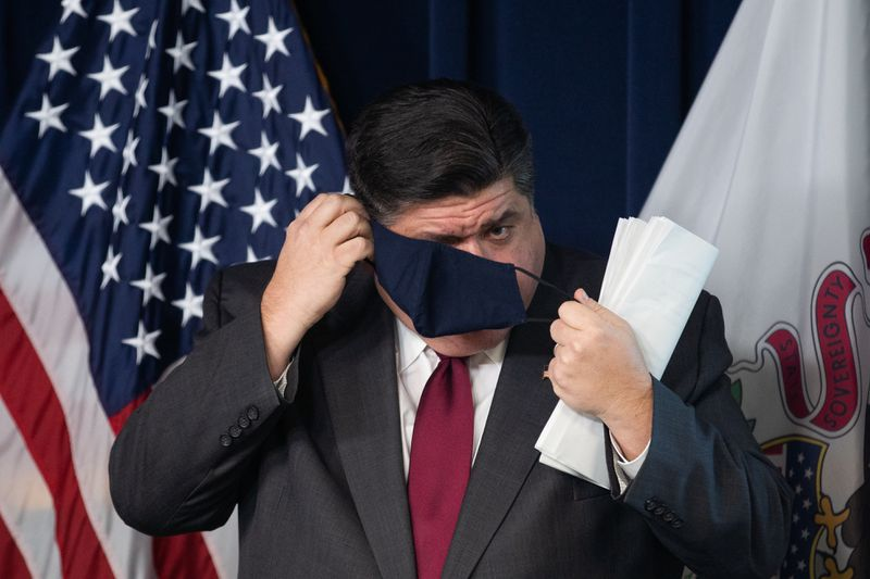 Gov. J.B. Pritzker puts on a mask during a briefing at the James R. Thompson Center in the Loop in November.