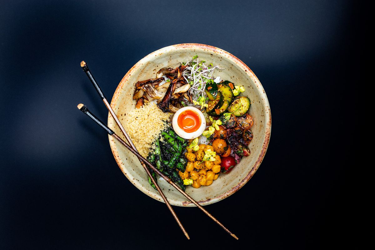 An overhead shot of a ceramic bowl with Japanese food inside.