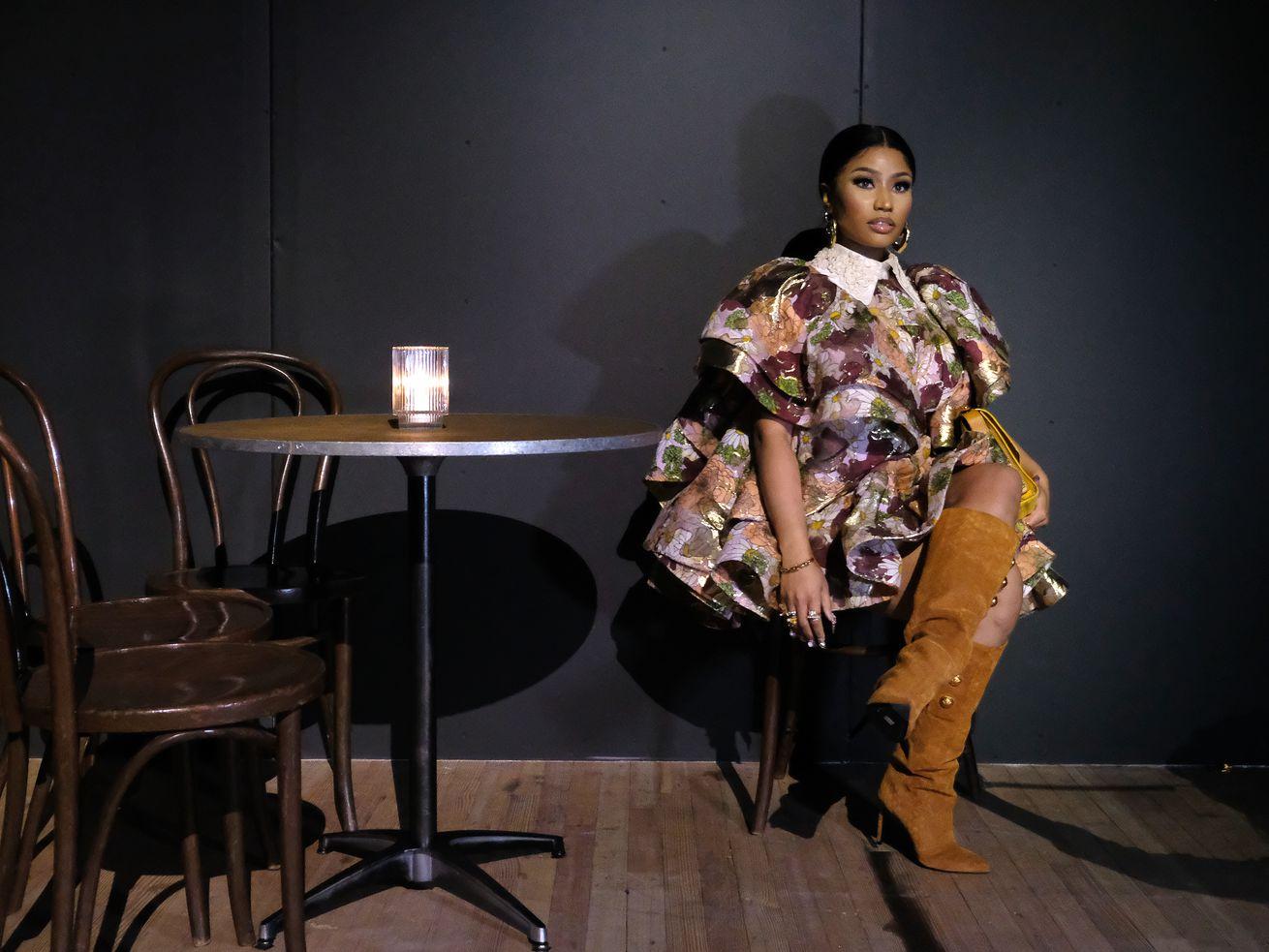 Nicki Minaj sitting alone at a cafe table.