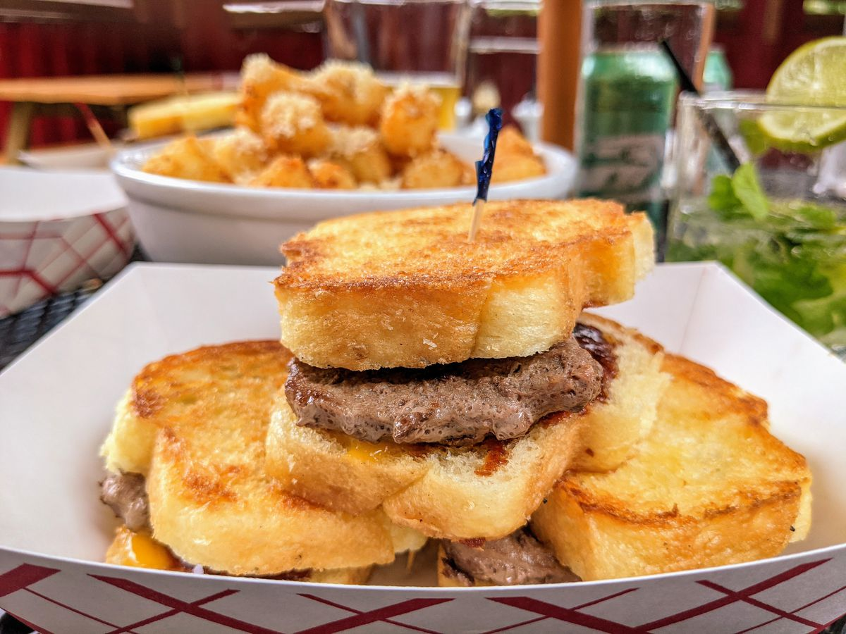 A stack of mini burgers on buttery toast sit in a white paper container on a patio table, with a big white bowl of tater tots and a mojito visible in the background.